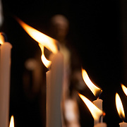Candle flames seemingly point the way inside St. Walltrude cathedral in Mons with an iconic statue in the background.