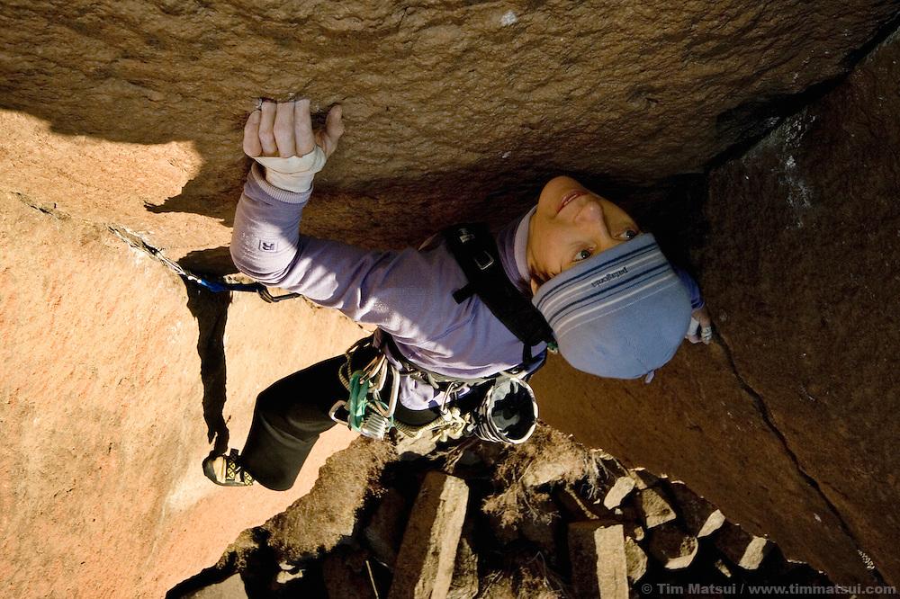 A caucasian woman climbing basalt cracks in Oregon...