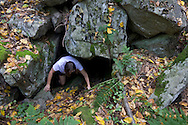 Warwick, New York - A hiker climbs out of the entrance to a cave at Fuller Mountain Preserve as part of the 2012 Hudson River Valley Ramble on Sept. 15, 2012. The preserve is owned and managed by the Orange County Land Trust.