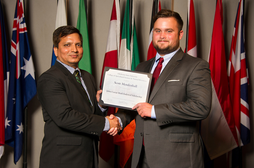 Oklahoma City native Scott Mendenhall (right), a landscape management major, receives an Oklahoma State University Julius Caesar Matli Endowed Scholarship from OSU associate professor Gopal Kakani (left) at the university's recent College of Agricultural Sciences and Natural Resources Scholarships and Awards Banquet. The scholarship is part of more than $1.4 million in scholarships and awards presented to CASNR students for the 2016-2017 academic year. (Photo by Todd Johnson)