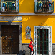 Woman walking past a colourful house in Puebla, Mexico