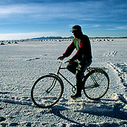 P&aacute;nfilo  Marques  that lives in population of Colchani internal every day through several km in the salar for fourteen years to be going to be employed at the extracion of of salt.  Salar de Uyuni ( Uyuni salt flat ) . Department  of Potos&iacute;  ( Los Lipez).  South West  Bolivia. <br /> Adult Altiplano America Andes Arid  Aridity Barren  Bicycle Bolivia Color Colour Cone  Day Daytime  Department  Desert Desolate Desolation Dry  Exterior Extraction  Geography Hard Heat Highlands  Horizon Horizontal Human  Latin America Lake  Los Lipez Male Man Men Miner Mining Nature  Resource  Natural  One Outdoors Outside  Pan People  Person Pyramide Potos&iacute;  Production  Region Resource Rural Salar de Uyuni  Salt Flat  Salt Pan  Salt lake  Scenic Seasoning  Single Shape South America  Southwest  Sud Sunglasses  Surface Travel  West White Work  Worker Working