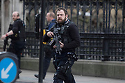 UNITED KINGDOM, London: 22 March 2017 An armed police officer walks in front of the gates of Parliament after a suspected terror incident outside the Houses of Parliament in Westminster, London earlier today. It is reported that there has been at least one fatality. Rick Findler / Story Picture Agency