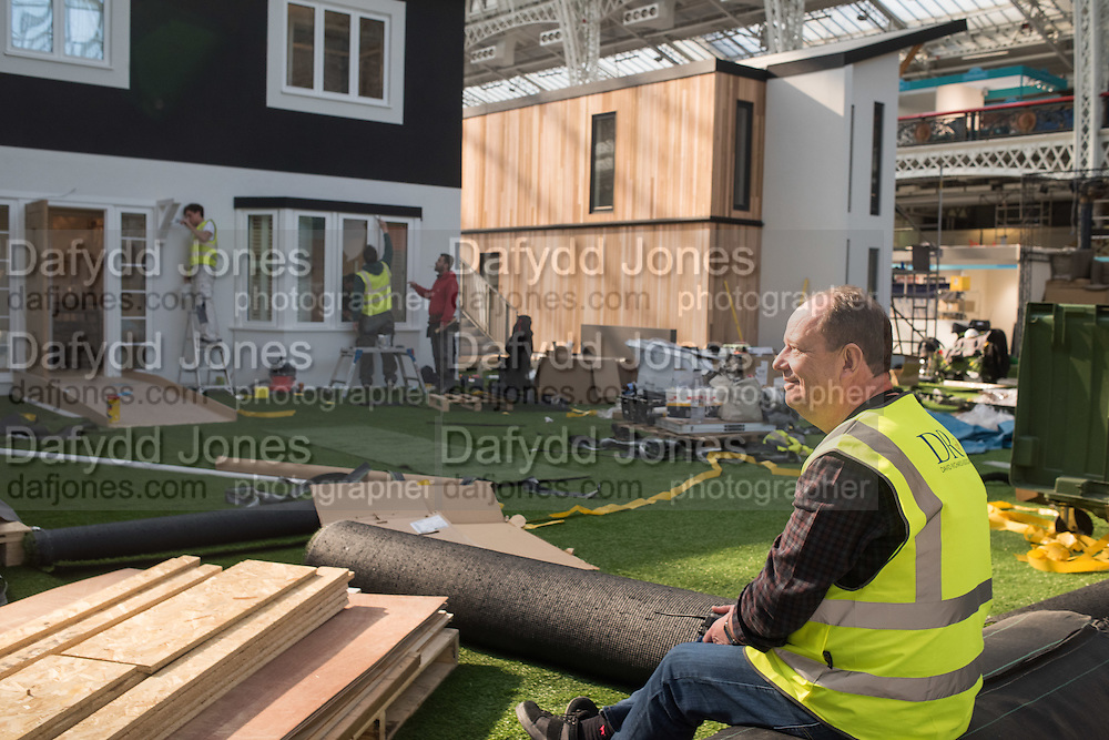David Richards project manager of the houses behind him, Day before the opening of the 2016 Ideal Home Exhibition. Kensington Olympia, 17 March 2016