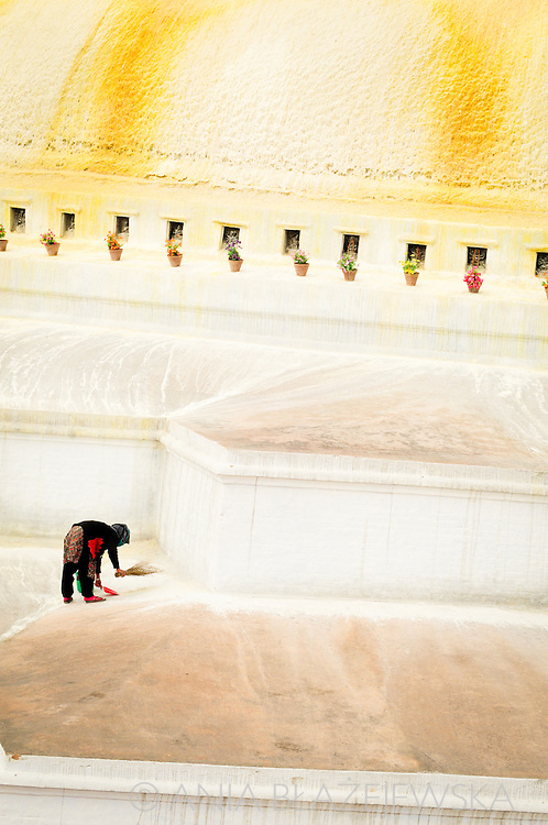 Nepal, Kathmandu. Women sweeping the Boudnath Stupa - the more important centre of the tibetan buddhism in Nepal.