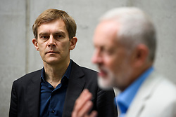 © Licensed to London News Pictures. FILE PICTURE: 10/07/2016. London, UK. Director of Strategy SEUMAS MILNE watches Labour Party Leader JEREMY CORBYN as he speaks to media outside BBC Broadcasting House in London after appearing on the Andrew Marr Show, on July 10, 2016. A BBC Panorama documentary, focusing on alleged anti semitism in the Labour Party is due to run this evening.   Photo credit: Ben Cawthra/LNP