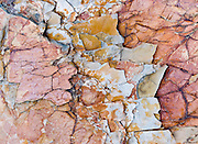 Billion-year-old rock breaks into blue, orange, and red patterns in Glacier National Park, Montana, USA. Rocks in the park are primarily sedimentary layers deposited in shallow seas over 1.6 billion to 800 million years ago. During the tectonic formation of the Rocky Mountains 170 million years ago, the Lewis Overthrust displaced these old rocks over newer Cretaceous age rocks. Since 1932, Canada and USA have shared Waterton-Glacier International Peace Park, which UNESCO declared a World Heritage Site (1995) containing two Biosphere Reserves (1976).
