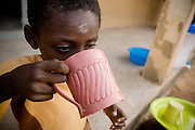 A child drinks from a plastic mug.Northern Ghana, Wednesday November 12, 2008.