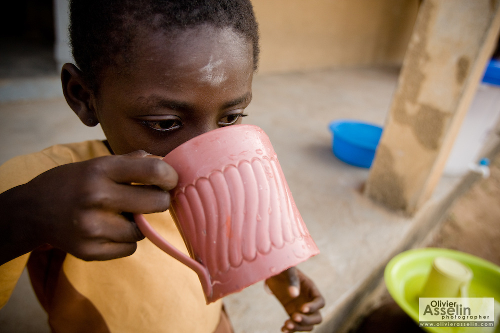 A child drinks from a plastic mug.Northern Ghana, Wednesday November 12, 2008.