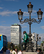 African man poses for photograph on Dublin's O'Connell Bridge. He jumped up on the bridge wall, luckily no police (gardai) around to pose for a photograph. I actually first saw him through the lense - I was photographing the lamp standard and Liberty Hall. So he was photographed twice!..