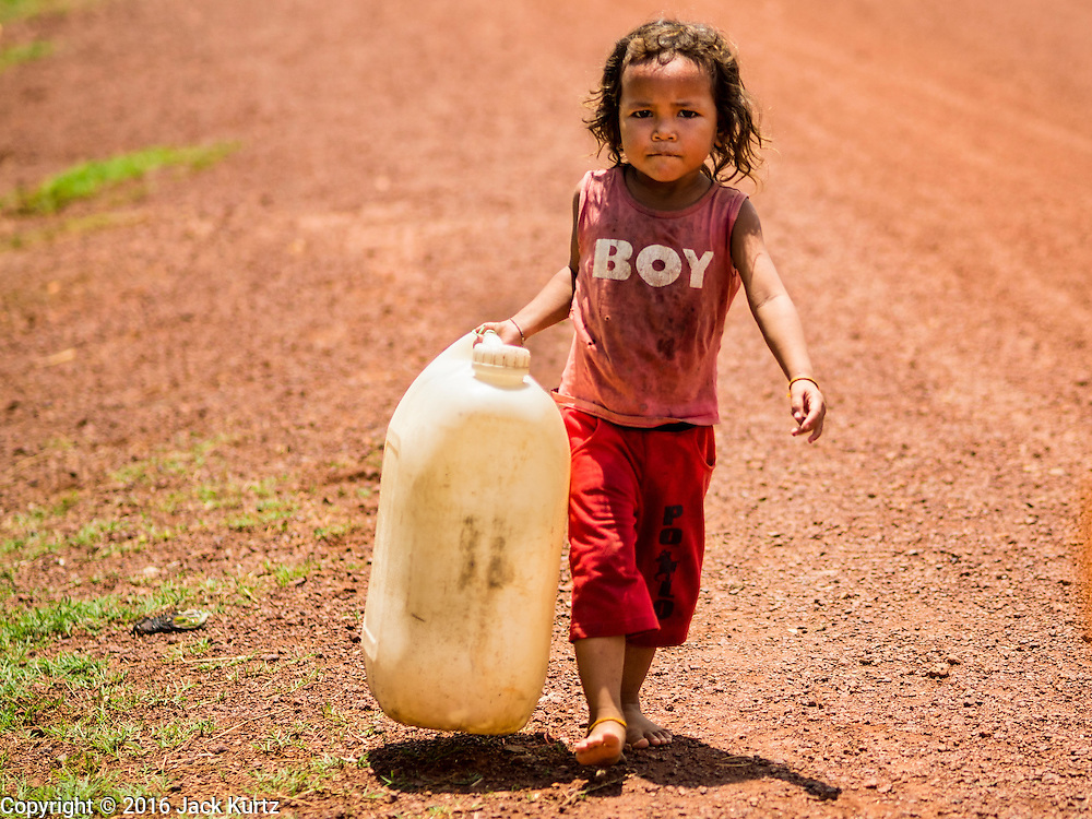 03 JUNE 2016 - SIEM REAP, CAMBODIA: A child carries an empty water jug to a water distribution point in Sot Nikum, a village northeast of Siem Reap. Wells in the village have been dry for more than three months because of the drought that is gripping most of Southeast Asia. People in the community rely on water they have to buy from water sellers or water brought in by NGOs. They were waiting for water brought in by truck from Siem Reap by Water on Wheels, a NGO in Siem Reap. Cambodia is in the second year of  a record shattering drought, brought on by climate change and the El Niño weather pattern. There is no water to irrigate the farm fields and many of the wells in the area have run dry.     PHOTO BY JACK KURTZ