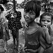 Poor Cambodian children gather near a market in Phnon Penh.