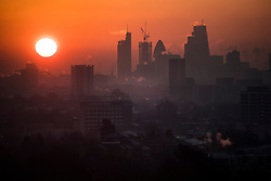 © Licensed to London News Pictures. 12/12/2017. London, UK. The sun rise over the city of London from Hampstead Heath in north London on a freezing morning. Temperatures across the the UK dipped overnight with some regions expected to drop to -13C (9F). Photo credit: Ben Cawthra/LNP