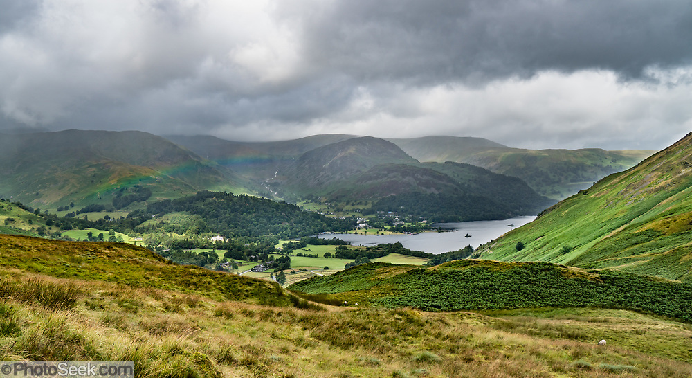 Rainbow over Ullswater, England's second largest natural lake. Lake District NP, UK, Europe. England Coast to Coast hike with Wilderness Travel, day 6 of 14: Ullswater to Kirkby Stephen, in Lake District National Park, United Kingdom, Europe. Hiking 10 miles with 2600 feet cumulative gain in the fells of Lakeland brought us over the highest Roman road in England, then down to the lakeshore of Haweswater. Overnight in Brownber Hall Country House near Kirkby Stephen, in Cumbria county. [This image, commissioned by Wilderness Travel, is not available to any other agency providing group travel in the UK, but may otherwise be licensable from Tom Dempsey – please inquire at PhotoSeek.com.]