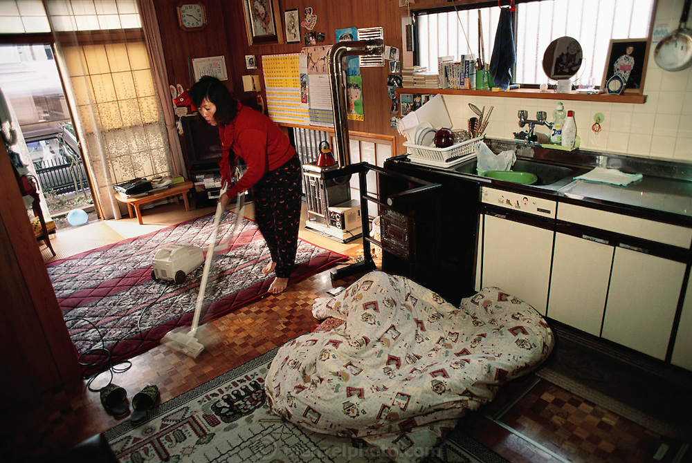 Sayo Ukita cleans up the house while her daughters are at school and husband is at work. Japan. Material World Project. The Ukita family lives in a 1421 square foot wooden frame house in a suburb northwest of Tokyo called Kodaira City.