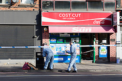 © Licensed to London News Pictures. 22/09/2016. LONDON, UK.  Forensic officers outside a newsagent near the scene. A man was found dead in the street following a suspected assault, near All Saints DLR station just before midnight last night.  Photo credit: Vickie Flores/LNP