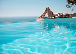 Woman sunbathing by a swimming pool with ocean in the background