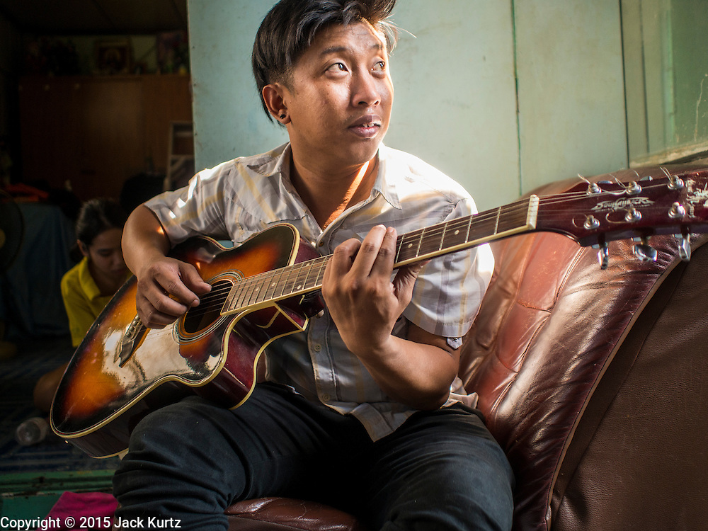 06 FEBRUARY 2015 - BANGKOK, THAILAND: SURACHAI SUKSON, 36, plays his guitar for his nephew in his home near Santa Cruz Catholic Church in the Thonburi section of Bangkok. Now the neighborhood around the church is known for the Thai adaptation of Portuguese cakes baked in the neighborhood. Several hundred Siamese (Thai) Buddhists converted to Catholicism in the 1770s. Some of the families started baking the cakes. When the Siamese Empire in Ayutthaya was sacked by the Burmese, the Portuguese and Thai Catholics fled to Thonburi, in what is now Bangkok. The Portuguese established a Catholic church near the new Siamese capital. There are still a large number of Thai Catholics living in the neighborhood around the church.       PHOTO BY JACK KURTZ