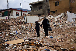 Nadia Al-Akhrass and her daughter Nour look through the rubble of the home where their relatives were killed in the war between Israel and Hezbollah, Aytaroun, Southern Lebanon, Oct. 23, 2006.