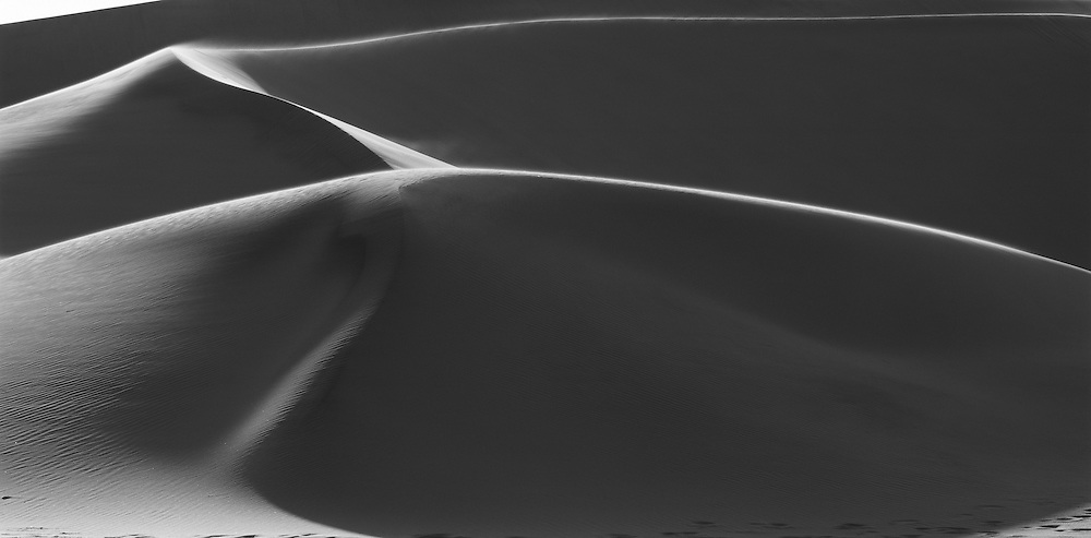 Namibia, Namib Desert, Setting sun lights curving sand dunes near coastal city of Walvis Bay