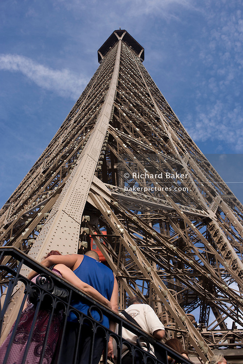 Tourists admire Paris below from the second level of the Eiffel Tower.
