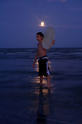 Boy standing on Galveston beach at night with his skimboard