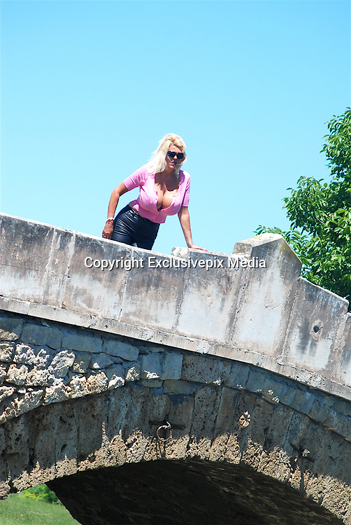 EXCLUSIVE<br /> <br /> Glamour model gran Sharon Perkins with 32MM breasts pictured in Bulgaria with her dogs as she takes a stroll in Bulgaria<br /> <br /> Photo shows: Sharon pictured at a bridge waiting for dogs in Bulgaria<br /> &copy;Exclusivepix Media