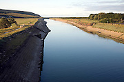 Straightened concrete lined channel of River Cuckmere as it nears its mouth, Exceat, Seaford, East Sussex, England