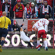 Lee Nguyen, New England Revolution, tumbles from a challenge by Richard Eckersley, New York Red Bulls, during the New York Red Bulls Vs New England Revolution, MLS Eastern Conference Final, first leg at Red Bull Arena, Harrison, New Jersey. USA. 23rd November 2014. Photo Tim Clayton