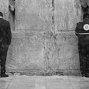 An Israeli emergency medical technician (EMT, R) and an ultra-orthodox man pray as snow and rain fall at The Western Wall on January 7, 2015 in Jerusalem, Israel. (Photo by Elan Kawesch)