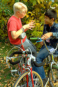 Cambodian American and friend age 14 sitting on bikes talking.  St Paul  Minnesota USA