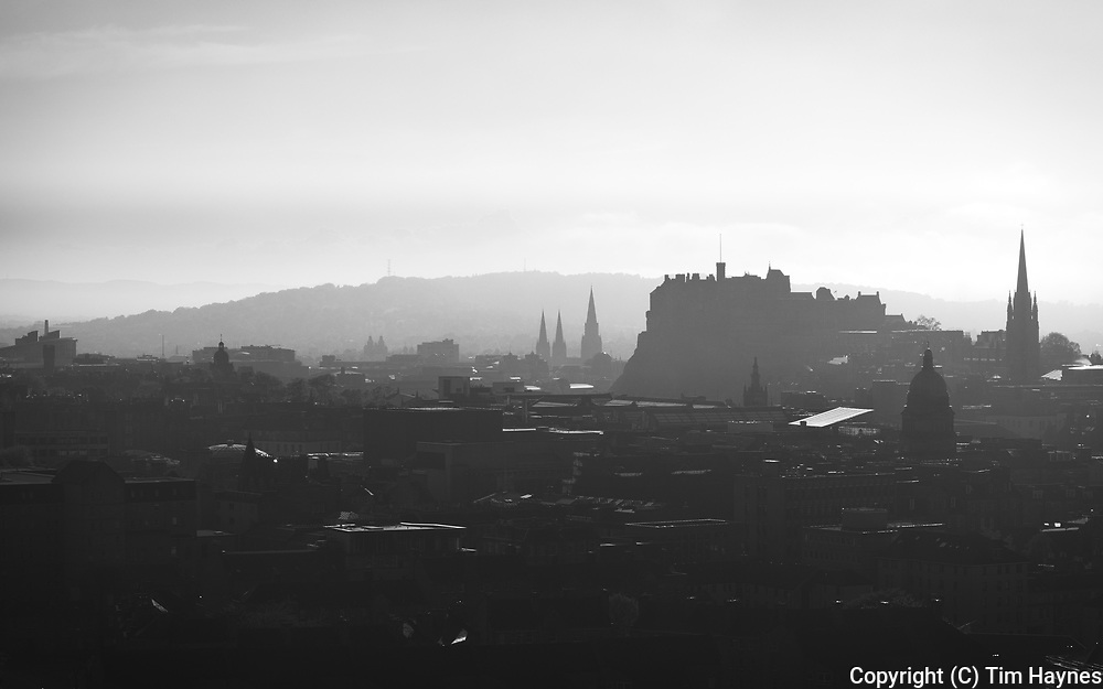 The iconic outline of Edinburgh Castle and city rooftops part-silhouetted against a bright hazy sky.