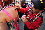 A firefighter applies a temporary tattoo to a woman during the Sant Yago Knight Parade in Tampa / Ybor City, Florida.  The event attracted more than 100,000 people.
