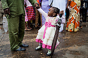 A young girl is pulling her father's hand after a Mass Service at Saint Theresa's Christian Catholic Church in Jos, Plateau State, Nigeria. Saint Theresa's is the first Christian Catholic Church built in Jos, in 1923.