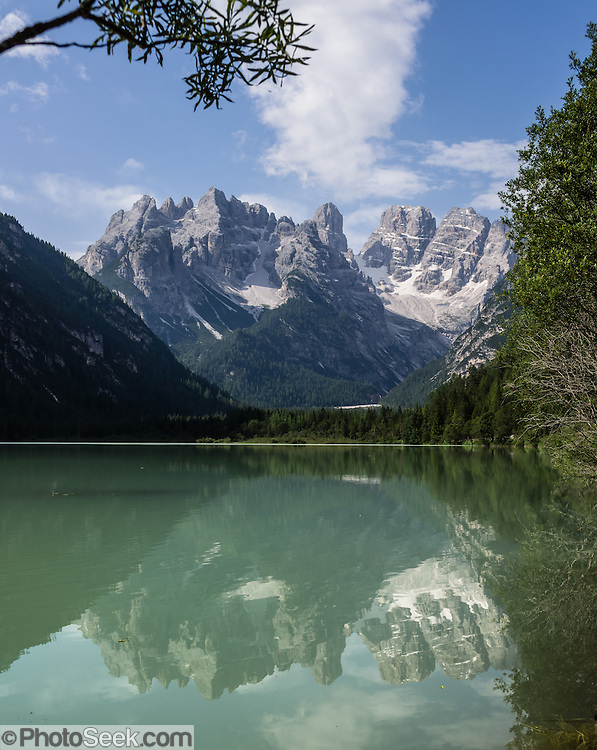 The Cristallo Group reflects in Lago di Landro (Dürrensee) is in Val di Landro/Höhlensteintal (in the watershed of Val Pusteria/Pustertal), in Tre Cime/Drei Zinnen Nature Reserve, in Trentino-Alto Adige/Südtirol (South Tyrol) region of Italy. Cristallo is largely formed from the Upper Triassic dolomitic rock Dolomia principale. Cristallo mountain group was formed during Cretaceous, as were the Dolomites in general, due to the collision between the African and European continents. The Dolomites are part of the Southern Limestone Alps, in northern Italy, Europe. UNESCO honored the Dolomites as a natural World Heritage Site in 2009.