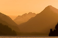 Evening light bathes the mountains in pink and mauve hues around Muchalat Lake, a large lake northeast of Gold River on Vancouver Island.  British Columbia, Canada.