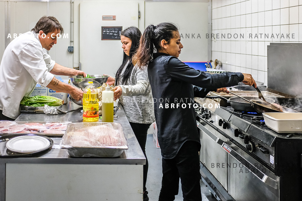 Trainee chefs Shania Austin (Right) and Latisha Austin (Centre) work in the kitchen while being watched by chef Nick Fleming (Left) at the Aboriginal Youth Sport and Recreation centre on Gertrude Street in Melbourne, Australia, September 1, 2017. Shania Austin (Right) and Latisha Austin (Centre) are both studying for a certificate two in Hospitality and are training at the Charcoal Lane Restaurant. Asanka Brendon Ratnayake for the New York Times