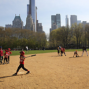 Youngsters baseball training during a warm spring day in Central Park, Manhattan, New York, USA. Photo Tim Clayton