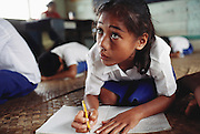 In Western Samoa, 10-year-old Teuila Lagavale attends math class where the uniformed students sit on mats woven from coconut leaves. The Lagavale family lives in a 720-square-foot tin-roofed open-air house with a detached cookhouse in Poutasi Village, Western Samoa. Material World Project.