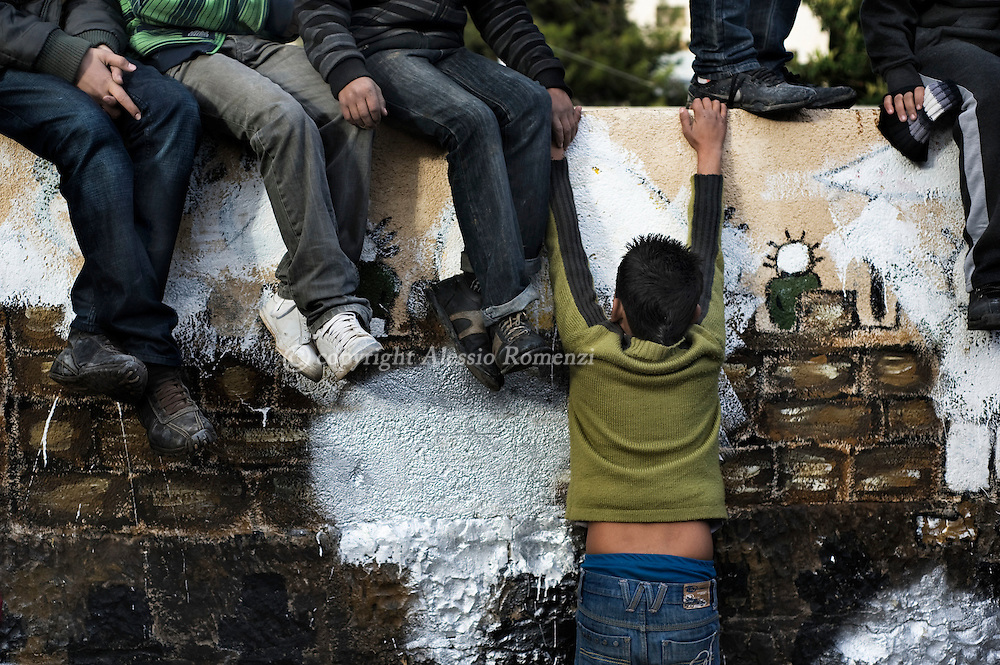 Palestinian youths sit in front of houses where Jewish settlers reside during a demonstration in the east Jerusalem neighborhood of Sheikh Jarrah, Friday, Dec. 18, 2009.  Ten activists were arrested during a protest against the eviction of Palestinians in predominantly Arab east Jerusalem..© ALESSIO ROMENZI