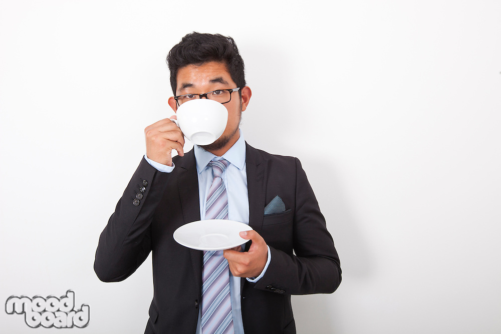 Portrait of young businessman drinking coffee over white background