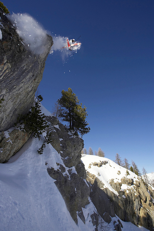 Male Skier jumps from rock. Serre Chevalier.France