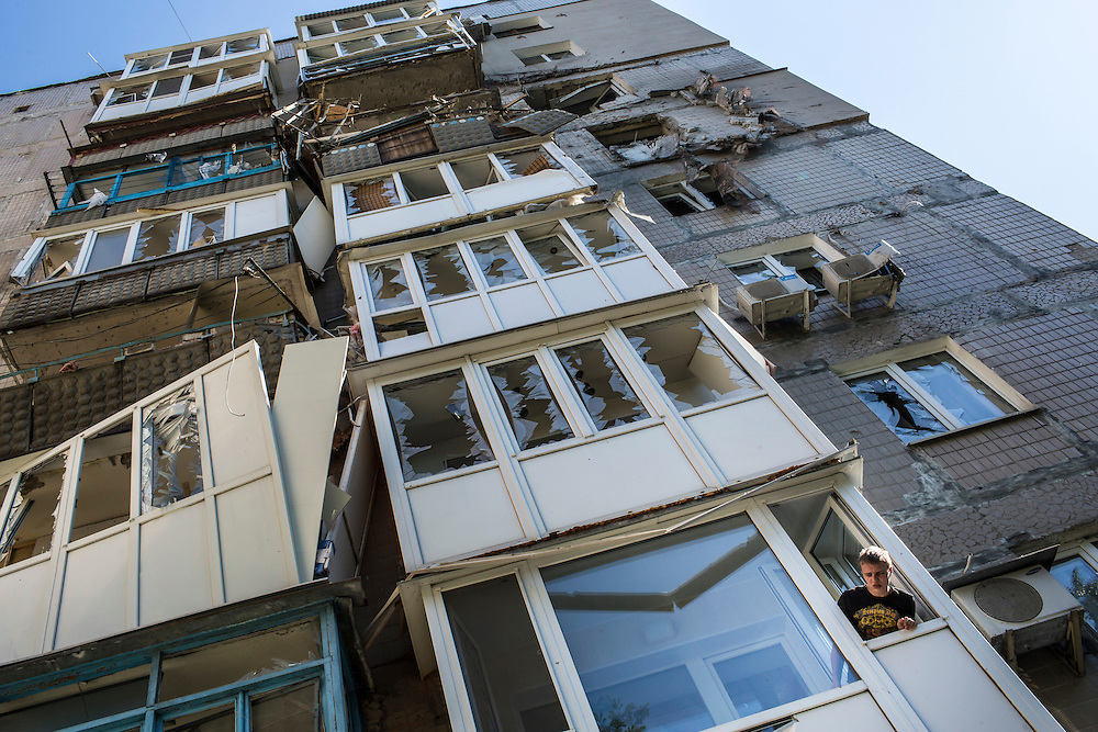 A man leans out the window of an apartment building that was hit by a supsected grad rocket strike on Tuesday, July 29, 2014 in Donetsk, Ukraine.