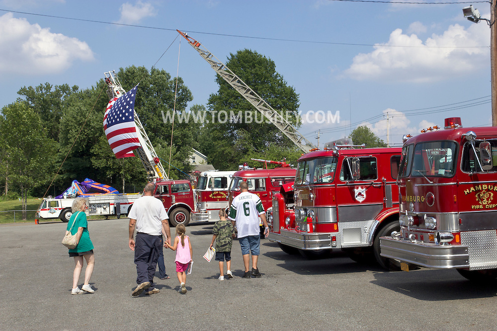 Circleville, New York - People walk past antique fire trucks on display at the Catskill Fire Cats 36th Annual Muster on Aug. 4, 2012.