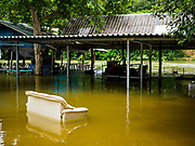 09 AUGUST 2018 - KAENG KRACHAN, PHETCHABURI, THAILAND: A couch sits in flood waters at flooded resort below Kaeng Krachan Dam on the Phetchaburi River. The Phetchaburi River flows from Kaeng Krachan Dam to the Gulf of Siam through several towns including Ban Lat, Phetchaburi (the capital of Phetchaburi province) and Ban Laem. Government officials have warned residents of those towns that their towns will flood because the reservoir behind the dam is approaching capacity. Ban Lat and Phetchaburi could be flooded for several weeks. Residents of Ban Laem have been warned that their community could be inundated for over a month. Dams in Kanchanaburi province, west of Phetchaburi, are also approaching capacity and flooding is also expected in that area.   PHOTO BY JACK KURTZ