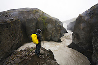 Hiker by river Kringilsá in Öræfi, Highlands of Iceland. Kringilsá is a glacier river that will largely disappear due to the Hálslón resovoir that is being made for Kárahnjúkar Power Plant.<br />