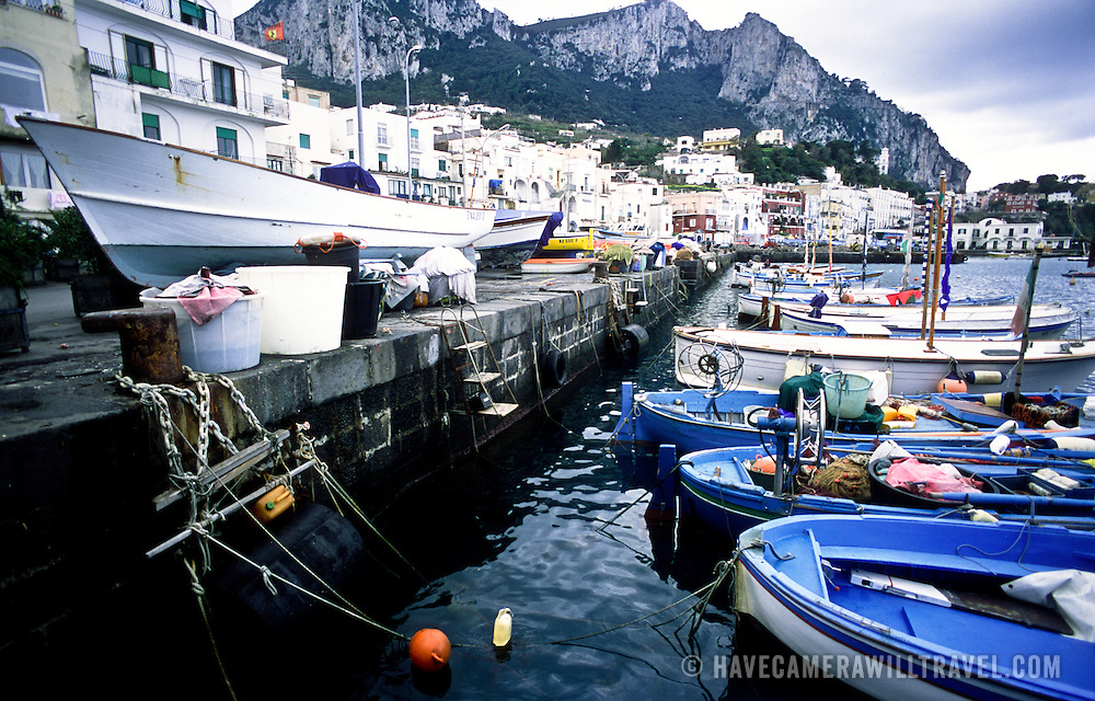 Wide angle photos of Marina Grande waterfront on the island of Capri, with a row of wooden fishing boats tied up to the waterfront dock and others on the dock for repair. In the distance are the ragged mountains of the island.