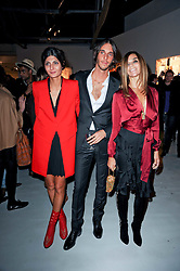 Left to right, Giovanna Battaglia, Vladimir Restoin Roitfeld and Carine Roitfeld  at a private view of Nicolas Pol's paintings entitled 'Mother of Pouacrus' held at The Dairy, Wakefield Street, London WC1 on 14th October 2010.