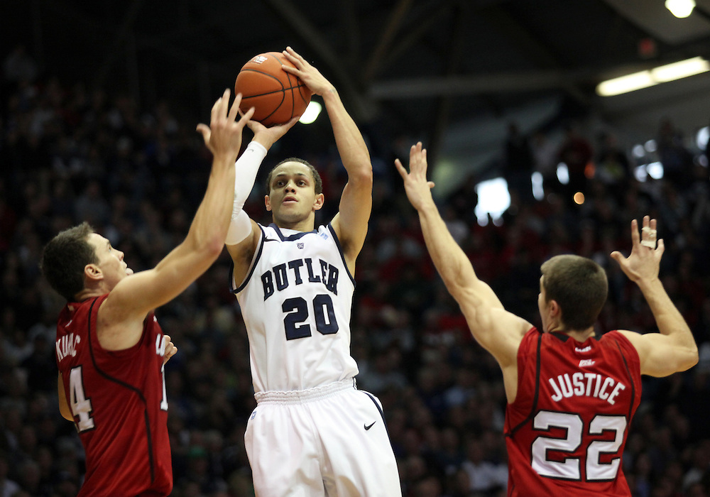 November 19, 2011: Butler's Chrishawn Hopkins shoots against Louisville's Kyle Kuric, left, and Elisha Justice, right, during the second half of the game at Hinkle Fieldhouse in Indianapolis, Ind. Louisville won 69-53.
