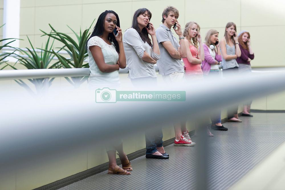 Seven students in a row using smartphones (Credit Image: © Image Source/Albert Van Rosendaa/Image Source/ZUMAPRESS.com)